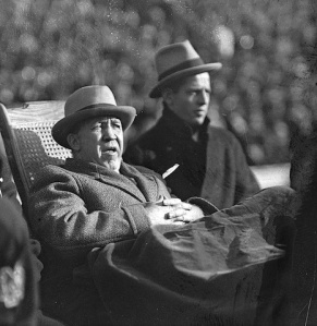 Coach Knute Rockne on the sidelines in a wheelchair.